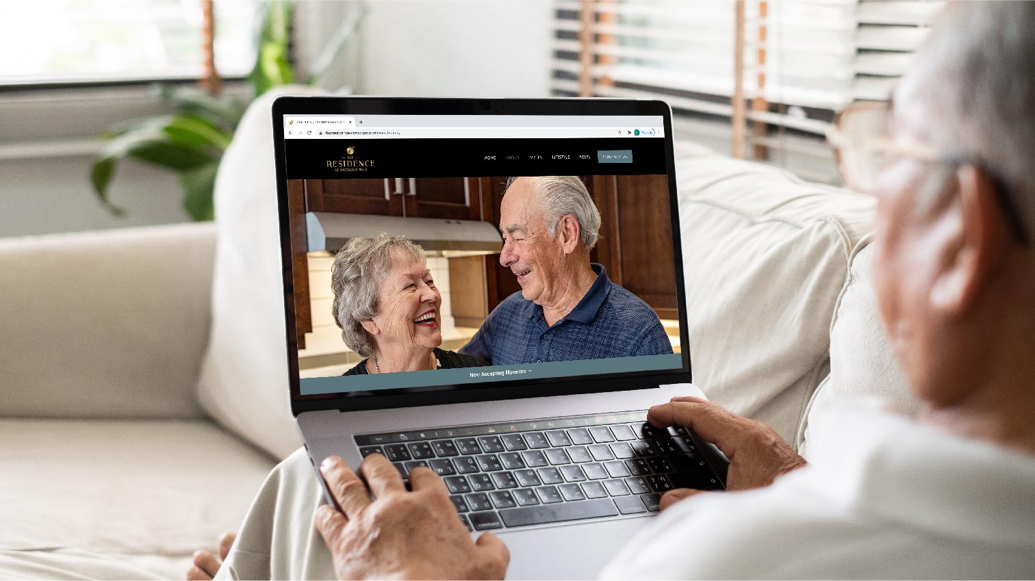 An elderly man visiting The Residence at Orchards Walk website on a laptop - White Canvas Design