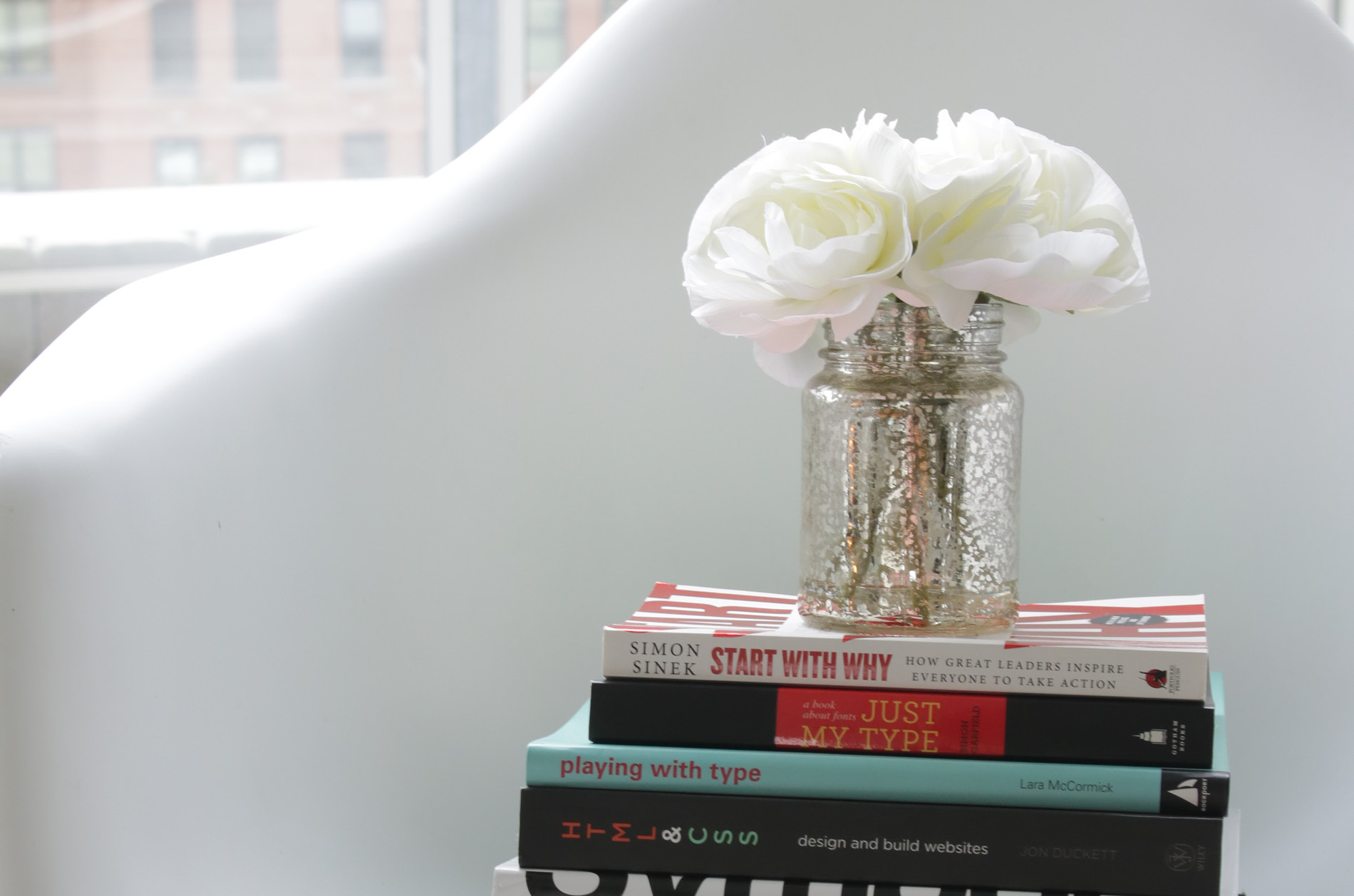 Various books and flowers in vase