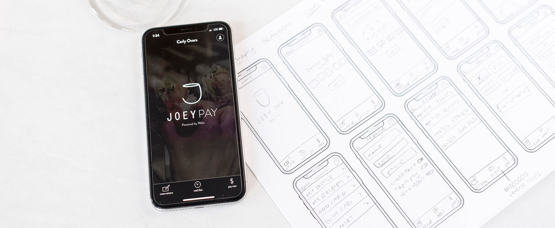 Joey Pay app on mobile beside sketches of the app design - White Canvas Design