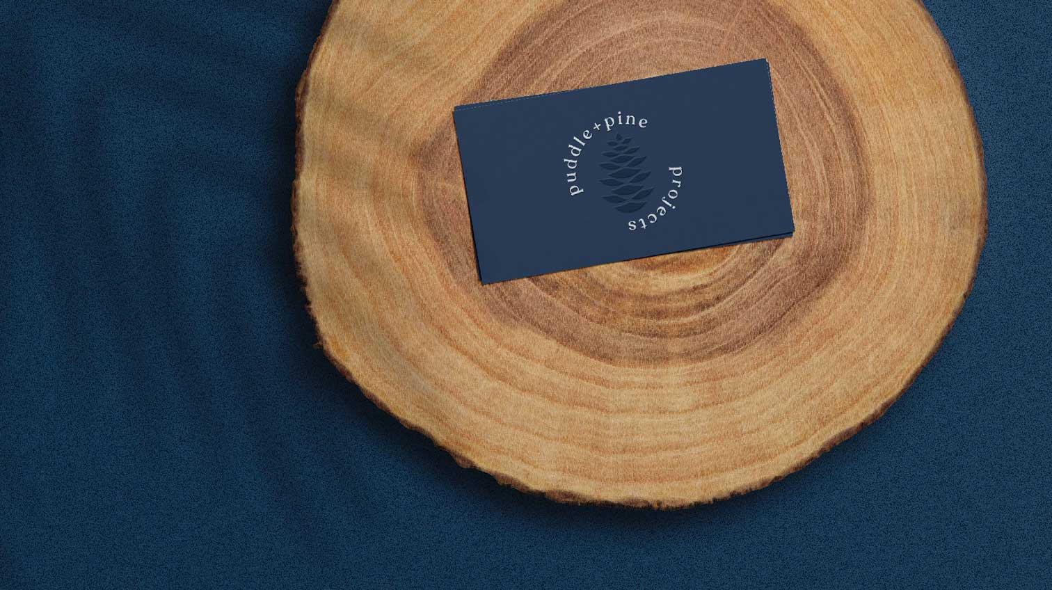 Puddle + Pine business card on top of a piece of wood - White Canvas Design