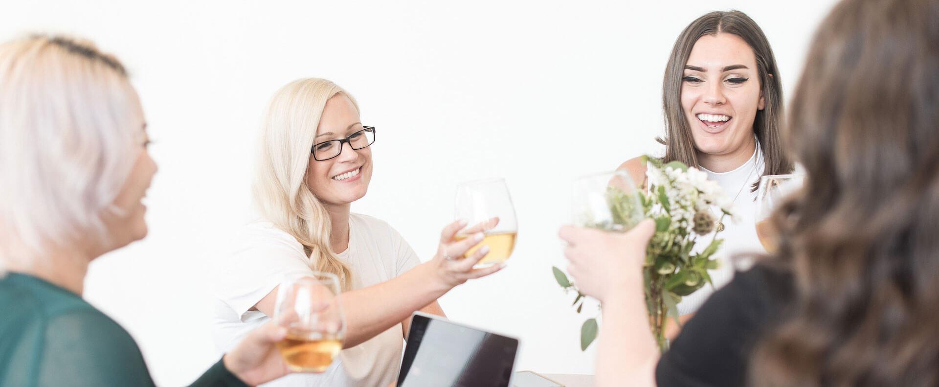 Four women (White Canvas Design Team) having a drink around the table - White Canvas Design