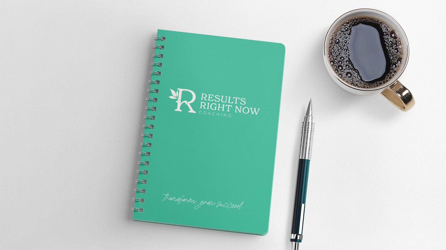 RRN notebook design on a table with coffee and a pen - White Canvas Design